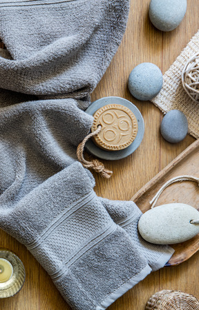 fresh shower and healthy bath concept with grey towel, ethnic solid soap, footcare object and zen stones over wooden background, top view