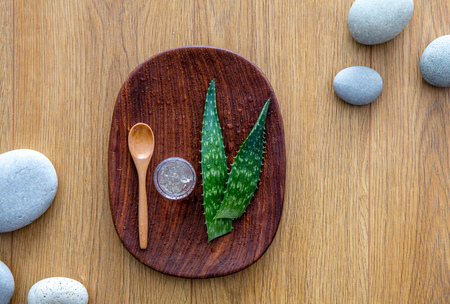 zen pebbles on wooden background for fresh organic aloe vera treatment extracted from the cut out plant for hydration, healthcare and sun burn