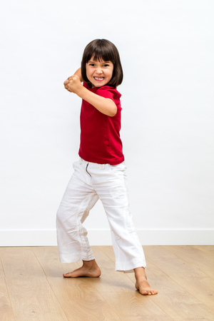 cheeky young child playing tiger or monster, expressing anger with sporty aggressive gesture, showing kids fighting body language over wooden floor, white background