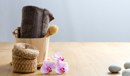 feng shui body and face care with wooden brush, towel, zen orchids and pebbles for relaxing bath and detox wellbeing, wooden copy space