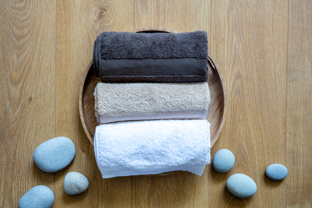 pampering towels and zen stones on round wooden background for concept of clean wellbeing, pure laundry or refreshing shower, above view still life