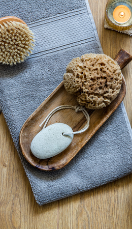natural sponge, footcare object and traditional dry brush for zero waste bodycare with zen candle, massage and minimalist shower, top view