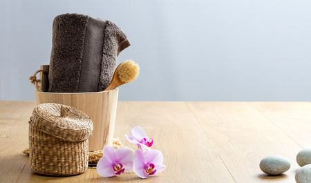 natural bath and shower products for zen bathroom. Wellness concept with rustic face dry brush, grey towel over zen flowers and pebbles on wooden copy space