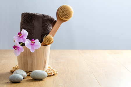 Healthy concept of beauty and design: exfoliate, cleanse, dry brush, detox for zen massage at the spa. Wooden copy space with orchids and stones Фото со стока