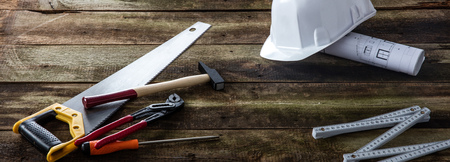Banner of house tooling gear for building, maintenance, craftsmanship and repairing with hard hat, architect blue print and carpentry tools over wooden background Фото со стока