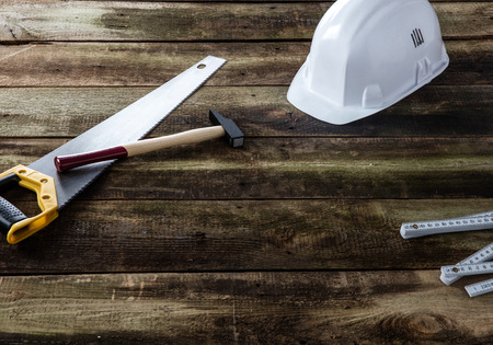 White construction helmet with saw, hammer and folding ruler for concept of builder, carpenter, engineer, craftsman job over rustic wooden background
