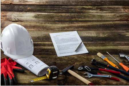 architect blueprint and building contract for new home owner signature set over wooden background with many construction, craftsman and hardware tools Фото со стока