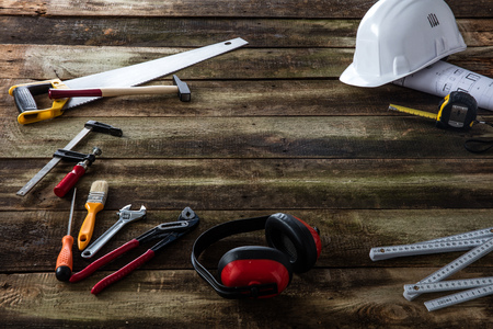 Display concept of safety gear, architect blue print and hardware tools such as saw, folding meter and wrench on wooden blank background