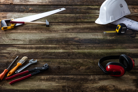 concept of DIY woodworking or house maintenance with construction tools and professional equipment over wooden background, copy space