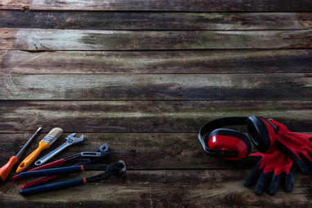 DIY, building or maintenance tools and safety equipment for wood know-how, carpentry or craftsman job over vintage wooden background
