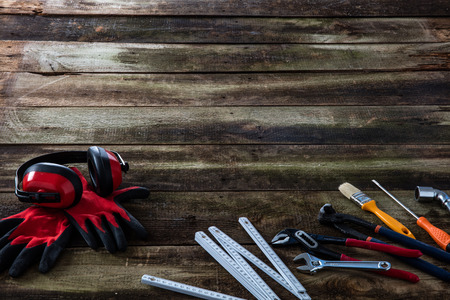 Safety ear protection and handy gloves with engineer or carpentry workman professional hardware tools on old wood for house and craftsman copy space background Фото со стока