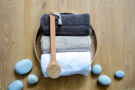 towels, body brush and zen pebbles on round wooden background for concept of fresh exfoliation, clean wellness and male Turkish bath, above view still life