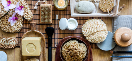 beauty and body care concept of traditional and zen objects for healthy shower or bath with natural sponge, loofah, olive oil soap, face cream and makeup brushes, top view