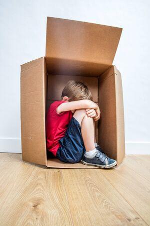 bambino solitario e curvo che piange in una scatola, si sente triste, rifiutato o spaventato, cerca protezione dal bullismo infantile o dall'educazione violenta