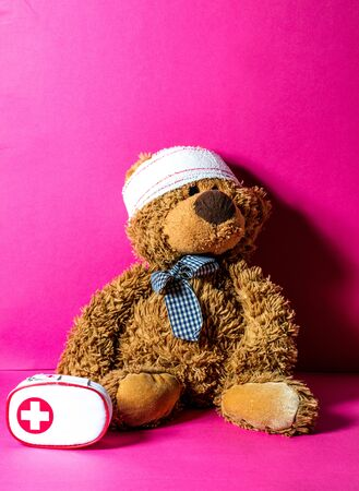 Teddy bear with bandage at the head and first aid kit for mishap concept of healthcare education over pink background Stock Photo