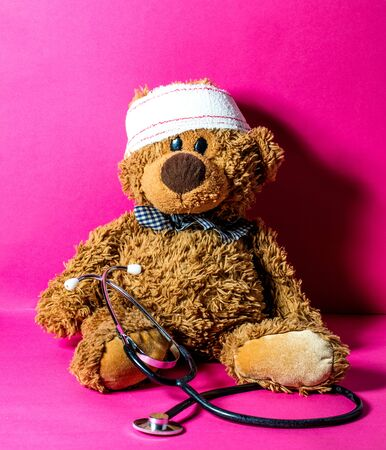 cute child's teddy bear with a head bandage and stethoscope for concept of domestic mishap and hospital treatment over nursing pink background Stock Photo