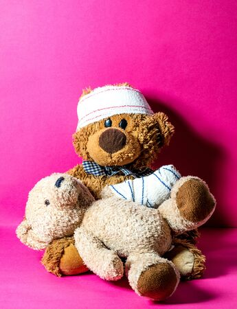 concept of child friendship and health assistance at the hospital with two injured teddy bears learning to treat each other, pink background Stock Photo