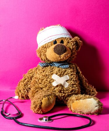 injured childs teddy bear with a belly and head bandage to check health, hurt feelings and body at the hospital or at doctors over nursing pink background