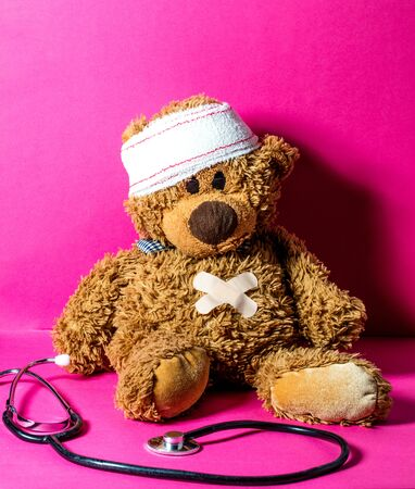 hurt childs teddy bear with a stomach and head bandage to check health, hurt feelings and body at the hospital for a treatment over nursing pink background