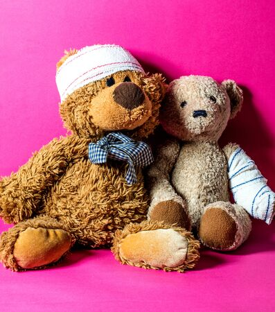concept of child friendship at the hospital with two ill teddy bears together and bandage for education to healthcare and domestic abuse