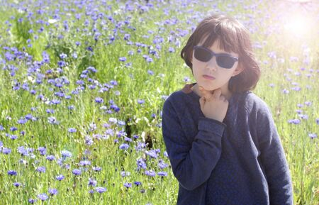 calm bored child with sunglasses thinking, daydreaming, having problems, seeking for ideas or inspiration over a blurred cornflower field, sun halo effect