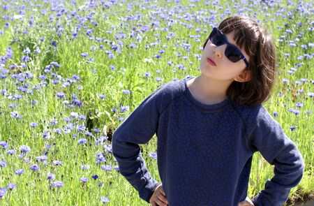 determined child with blue sunglasses standing with hands on hips questioning childhood future, issue with nature over a beautiful floral field, outdoor