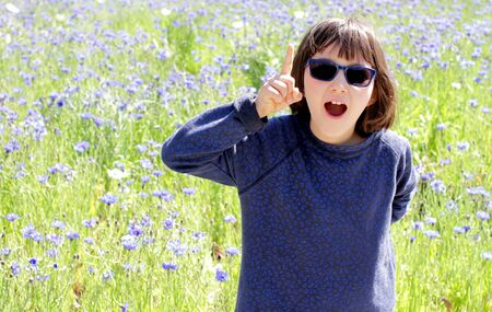 thrilled smart child with blue sunglasses raising her finger for playful surprise, creativity, question or fun expression over a sunny cornflower meadow, outdoor