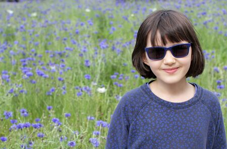 beautiful portrait of a smiling child with blue sunglasses and floral sweater over blurred natural cornflower field background for kid wellbeing