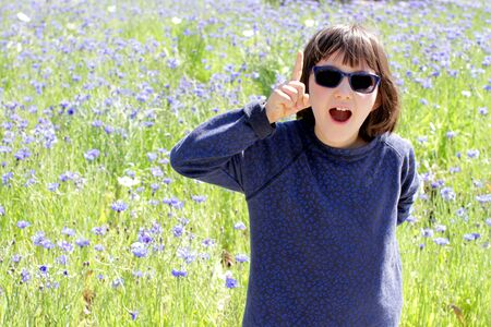 joyous smart child with blue sunglasses expressing a playful surprise, creativity, question or inspiration over a sunny cornflower park, outdoor