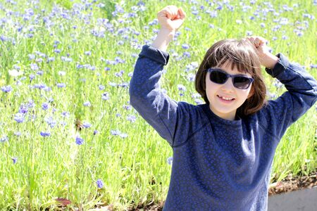thrilled young girl with blue sunglasses enjoying, showing her happiness for being in nature with a sunny blooming cornflower field at springtime Reklamní fotografie