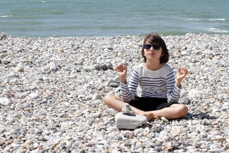 yoga child with summer sunglasses sitting on a pebble beach, meditating and breathing alone outdoor, seeking for calm on the ocean water front
