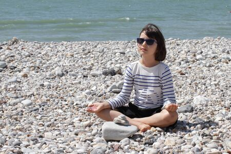 smiling young child with sunglasses sitting with quartz crystals in hands on a pebble beach and water front for energy, mindfulness, relaxation and silence