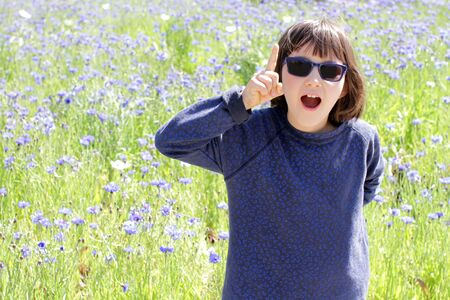 happy excited child with blue sunglasses expressing a playful surprise, creativity, humour, joy or inspiration over a sunny floral field, outdoor