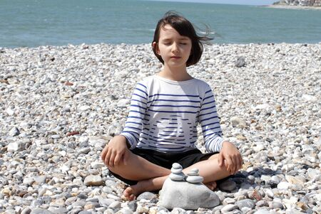 calm eyes closed child sitting with zen pebbles for mindfulness and meditation, relaxing on a mineral beach for energy, inner peace and energy, water background
