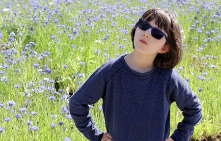determined child with blue sunglasses standing with hands on hips questioning, facing future or problems with nature over a beautiful floral meadow, outdoor Archivio Fotografico