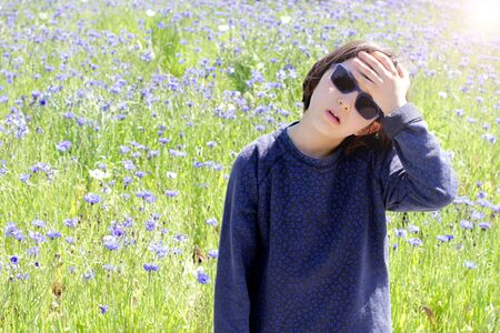 concerned child with sunglasses suffering from hot weather and pollution with blue floral meadow background at springtime, sun halo effect