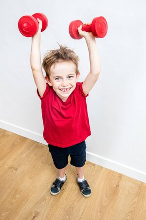 happy boy with tooth missing enjoying lifting up weights winning to express effort, success, joy, champion wellness, high angle view