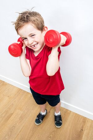 smiling boy with loose tooth expressing fun pride, lifting dumbbells to grow up with humour or muscle power, high angle view