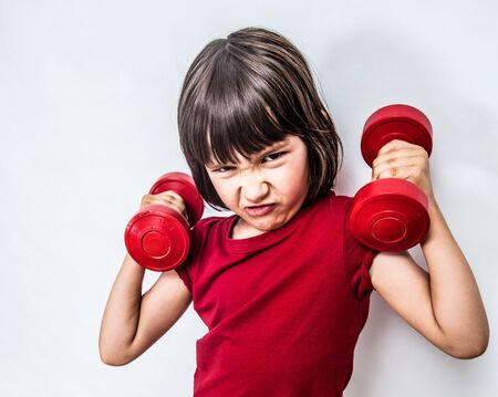 portrait of a mad frowning child expressing rage and violence with dumbbells for bully attitude, feminism, muscle power or education with humour, white background