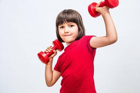 Niño divertido que disfruta levantando las manos con pesas para la actitud de niña-niño en el deporte que expresa éxito, poder, motivación u orgullo, fondo blanco.