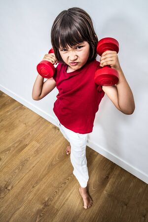 offended frowning child expressing rage and violence with dumbbells for bully attitude, feminism, muscle power or education, high angle view