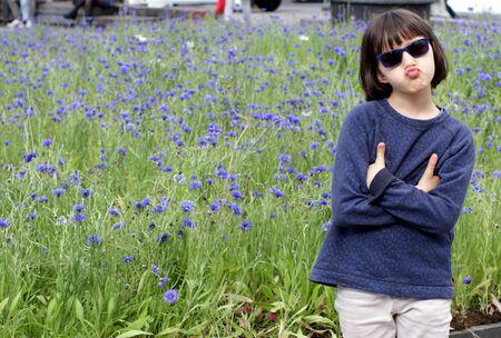 enfant heureux faisant la moue pour un doute maladroit avec des bras cool croisés avec un jardin de fleurs bleues et un fond de ville Banque d'images