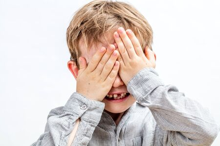 joyful smiling child with tooth missing hiding his face playing peekaboo, hide and seek, pretending  being invisible, isolated, white background 写真素材