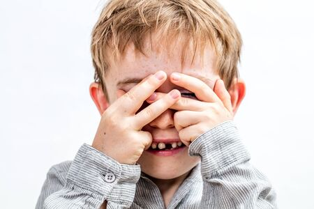 cute smiling child with tooth missing hiding his face to play peekaboo, hide and seek, pretending being a monster or invisible, isolated, white background 版權商用圖片