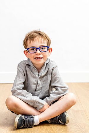 calm studious child with eyeglasses and a 6-year old missing tooth sitting crossed legs on a wooden floor with white background