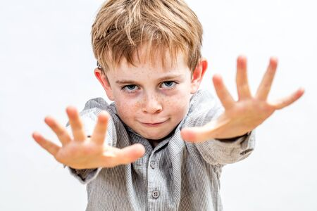 fun child pretending being a magician with illusion and determined hand gesture to express miracle or respect of boundaries, isolated white background