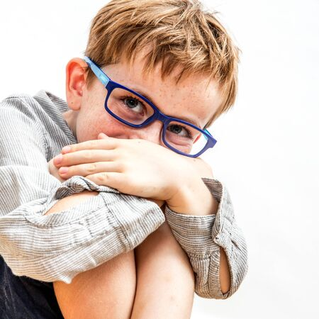 portrait of a cute shy boy with freckles and eyeglasses hiding his smile in his knees and hands for happiness, humour, wellness and joy of childhood, isolated white background