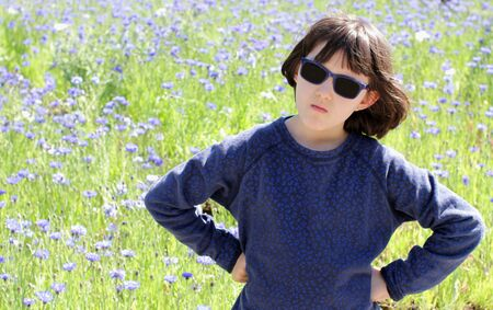 angry sulking boyish child standing with concerned hands on hips for responsibility statement, having a critical attitude facing nature issues over beautiful meadow Stockfoto