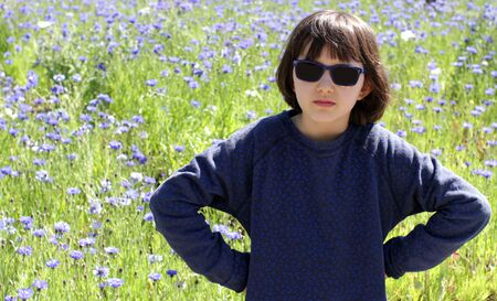 upset unhappy child determined for nature and childhood causes, standing with hands on hips and sunglasses, requiring adult responsibility over beautiful meadow Archivio Fotografico