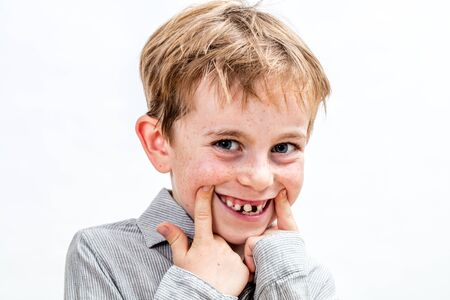 adorable boy with freckles giggling, playing with a fake toothless smile, studio portrait, isolated white background